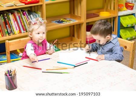 Two little kids drawing with colorful pencils in preschool at the table. Little girl and boy drawing in kindergarten