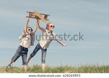 Two little kids playing with cardboard toy airplane in the park at the day time. Concept of happy game. Child having fun outdoors. Picture made on the background of blue sky.
