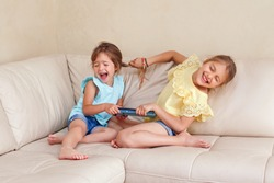 Two little mad angry girls sisters having fight at home. Friends girls can not share gadget tablet. Lifestyle authentic funny family moment of siblings quarrel life. Kids bad behaviour.