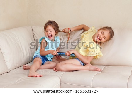 Two little mad angry girls sisters having fight at home. Friends girls can not share gadget tablet. Lifestyle authentic funny family moment of siblings quarrel life. Kids bad behaviour.  Foto stock ©