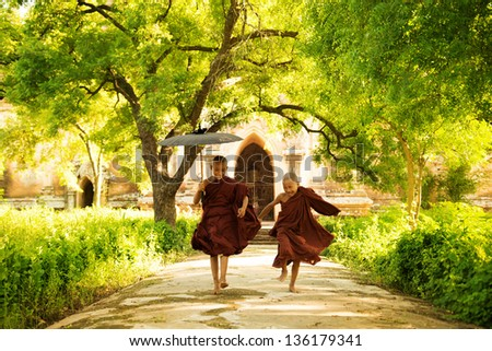 Two little monks running outdoors