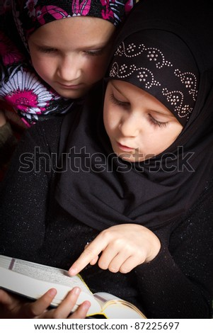 Two little muslim girls reading Holy Book Koran