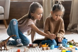 Two little 6s 7s sisters pretty daughters spend free playtime seated on carpet warm floor in modern living room play together wooden brick and dinosaurs toys set. Friendship, fun and leisure concept