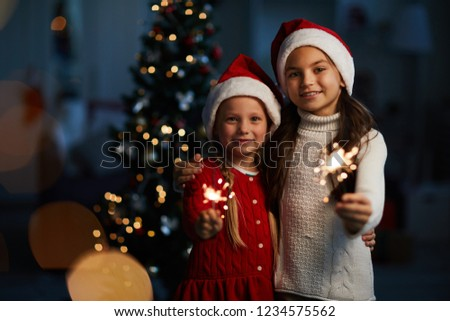 Two little Santa girls with burning bengal lights looking at you on background of decorated firtree #1234575562