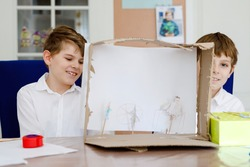 Two little school kids boy making paper doll theatre. Happy children and friends creating figures and performing stage play during quarantine time at home. Active creative siblings staying at home.