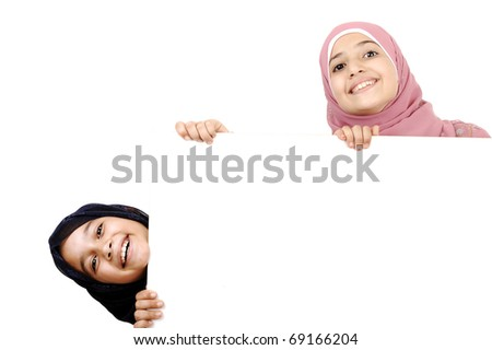 Two little schoolgirls holding a blank white sign for your message. Good for borders of articles or websites. Beautiful arabic muslim models. Isolated on white background.