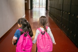 Two little schoolgirls with pink backpacks holding hands and standing in school corridor. Back view. Education or back to school concept