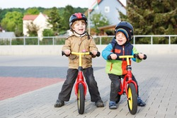 Two little siblings children having fun on bikes in city on vacations, outdoors.