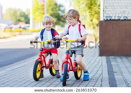 Two little siblings children having fun on bikes in city on vacations, outdoors. Brother kid boys riding with bicycles.