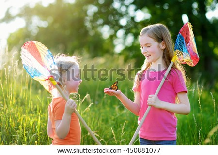 Two little sisters catching butterflies and bugs with their scoop-nets on beautiful sunny summer day