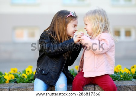 Two little sisters fighting outdoors #286817366