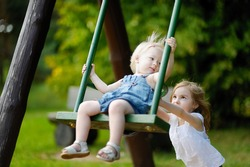 Two little sisters having fun on a swing on summer day