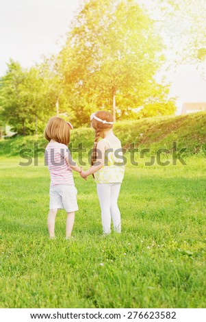Two little sisters holding hands standing in park on sunny day. Rear view of two five year old little girls in pastel clothes outdoors in nature. Vertical, retouched, vibrant colors.