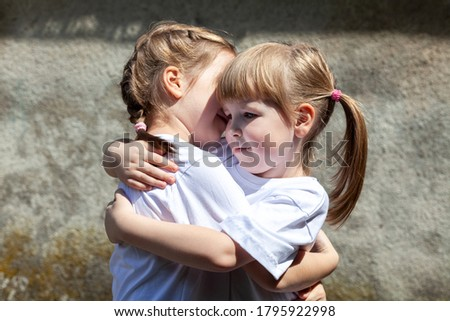 Two little sisters hugging each other, smiling. Happy young kids, siblings close together, portrait. White t-shirts, care, kindness, friendship concept Photo stock ©