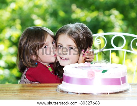 Two little sisters huging and celebrating birthday