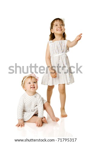 Two little Sisters looking up with interest isolated on white
