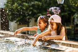 Two little sisters playing in the city square  fountain.They sprayed with water.Refreshing on hot summer day.