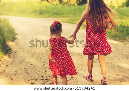 Two Sisters Holding Hands