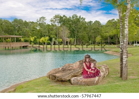 Two little sisters sitting on a large rock with pretty lack in background.