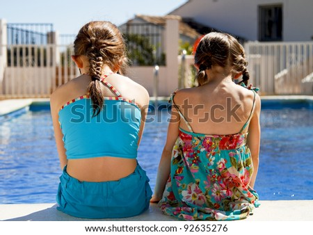 Two little sisters sitting side by side on the pool edge