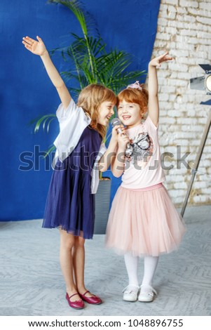 Two little smiling kids dance and sing a song in karaoke. The concept is childhood, lifestyle, music, singing, friendship. #1048896755