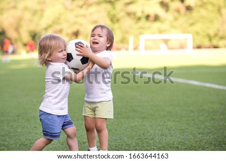 Two little toddlers arguing at football field or playground over soccer ball trying to take or grab ball. Conflict management, corporate fight metaphor and conflict resolving concept. Copy space Foto stock ©