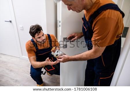 Two locksmith, repairmen, workers in uniform installing, working with house door lock using screwdriver. Repair, door lock service concept. Selective focus on hands and lock plate. Horizontal shot