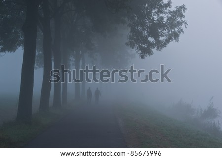 Two lonely people walking through the fog