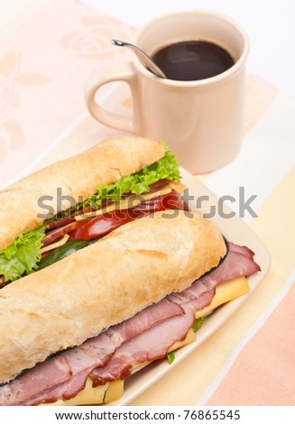two  long baguette sandwich with lettuce, vegetables, salami and cheese and a cup of coffee