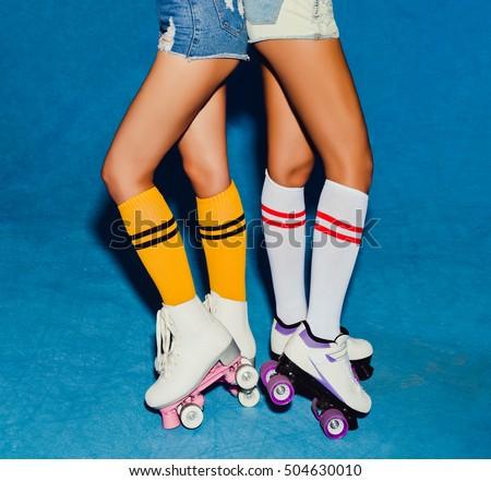 Two long-legged girls in knee socks, half-hose on roller skating vintage derby posing in the skatepark. Part of body.
