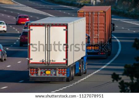 Two lorries, freezer and shipping container in motion on the motorway
