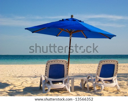 Two lounge chairs under a blue umbrella on the white sandy beach