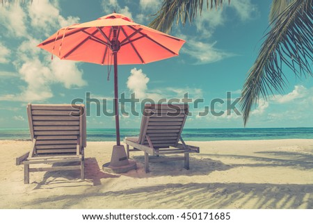 Two lounge chairs with sun umbrella on a beach under the palm trees in Maldives. Vintage Instagram effect #450171685