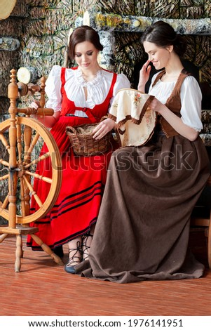 Two Lovely Caucasian Ladies  Posing With Spinning Wheel And Fancywork Hoop in Retro Dress In Rural Environment.Vertical Shot Stock photo ©