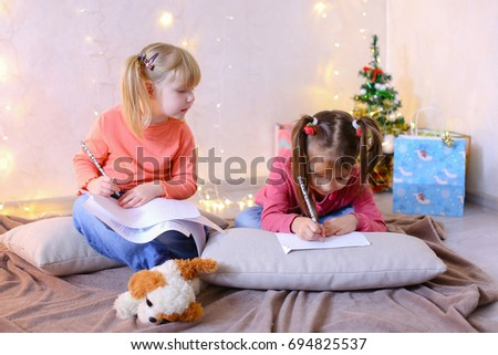 Two lovely children of girls with smiles on their faces and in good spirits dream of New Year gifts and write wishes for Santa Claus #694825537