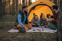 Two lovely couples sitting in front of their tent while camping and drinking hot beverage