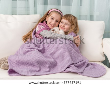 two lovely little girls covered with blanket embracing on sofa