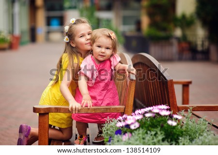 Two lovely little sisters outdoors in city at beautiful summer day hug and smile