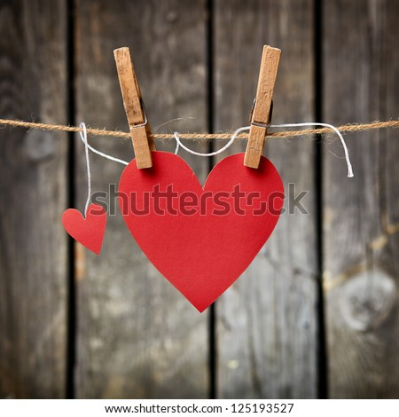 Two lovely red hearts big and small hanging on the clothesline On old wood background