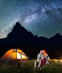 Two lovers hikers covered with a plaid sitting together near campfire and shines camp at night under stars and looking to the starry sky and Milky way. Silhouette of high mountains on background