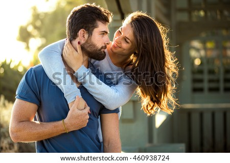 Two lovers in blue clothing in nature park outdoors hug and kiss