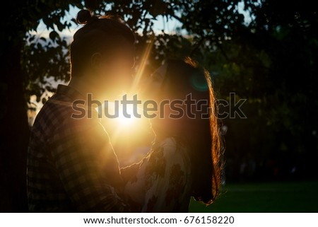 Two lovers in the back light. Silhouetted photo in the park. Love, relationship concept #676158220