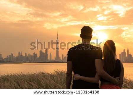 Two lovers looking at the city view during sunset. Travel concept.