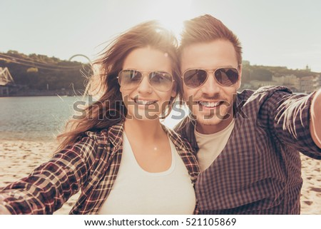 Two lovers making a selfie photo near the river, close-up phot #521105869