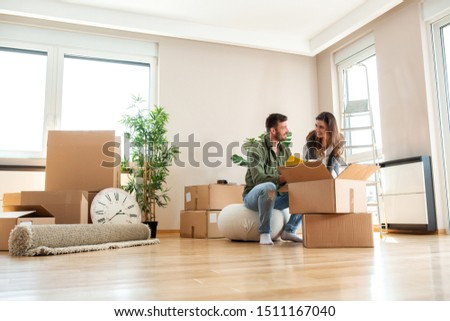 Two lovers moving in the new apartment and unpacking Foto stock ©