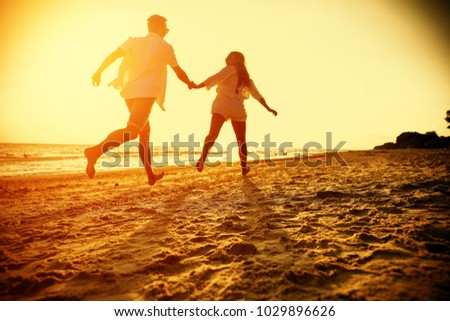 Two lovers on beach and summer golden sunset time.  #1029896626