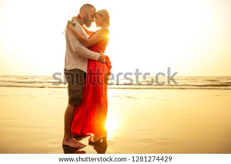 two lovers people at sunset by the sea romance and tenderness feelings first love date.man and woman blonde in a dress on the beach with a rose sun rays.Valentine's day and International Women's Day #1281274429