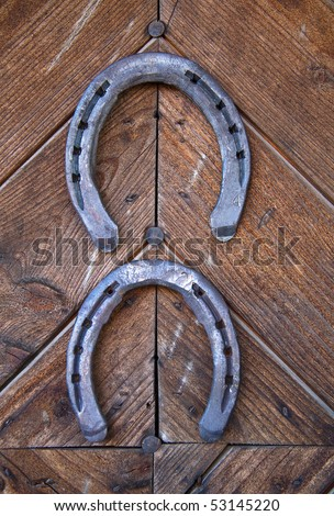 Two lucky horseshoes on wooden wall