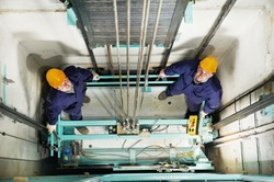 two machinist worker technicians at work adjusting lift with spanners in elevator hoist way