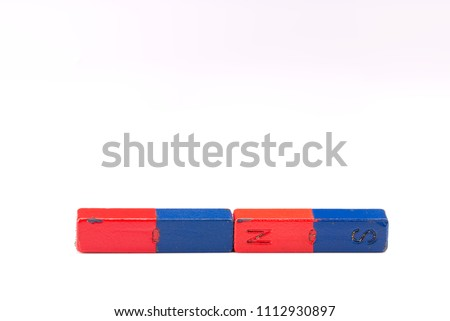 Two magnets attracting each other isolated on a white background. North – South attraction. Science scientific concept #1112930897